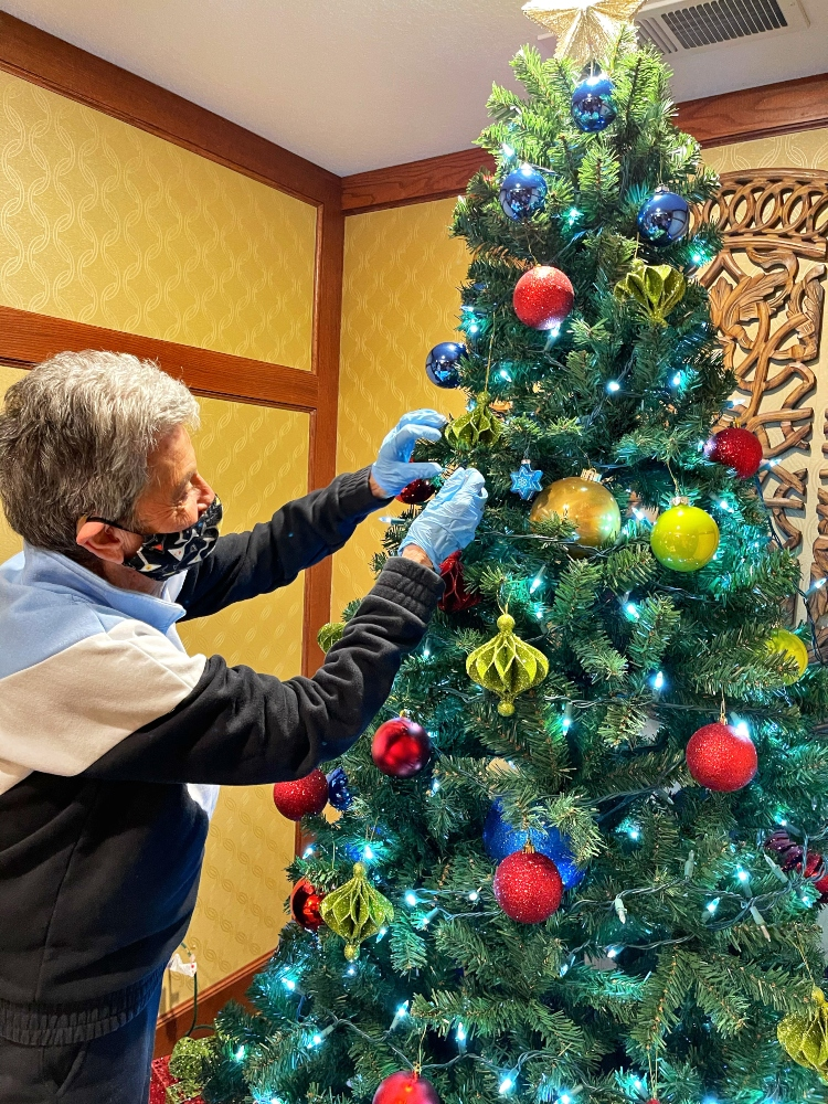 The Villas of Lilydale resident, Shirley G., helping decorate the community Christmas tree.